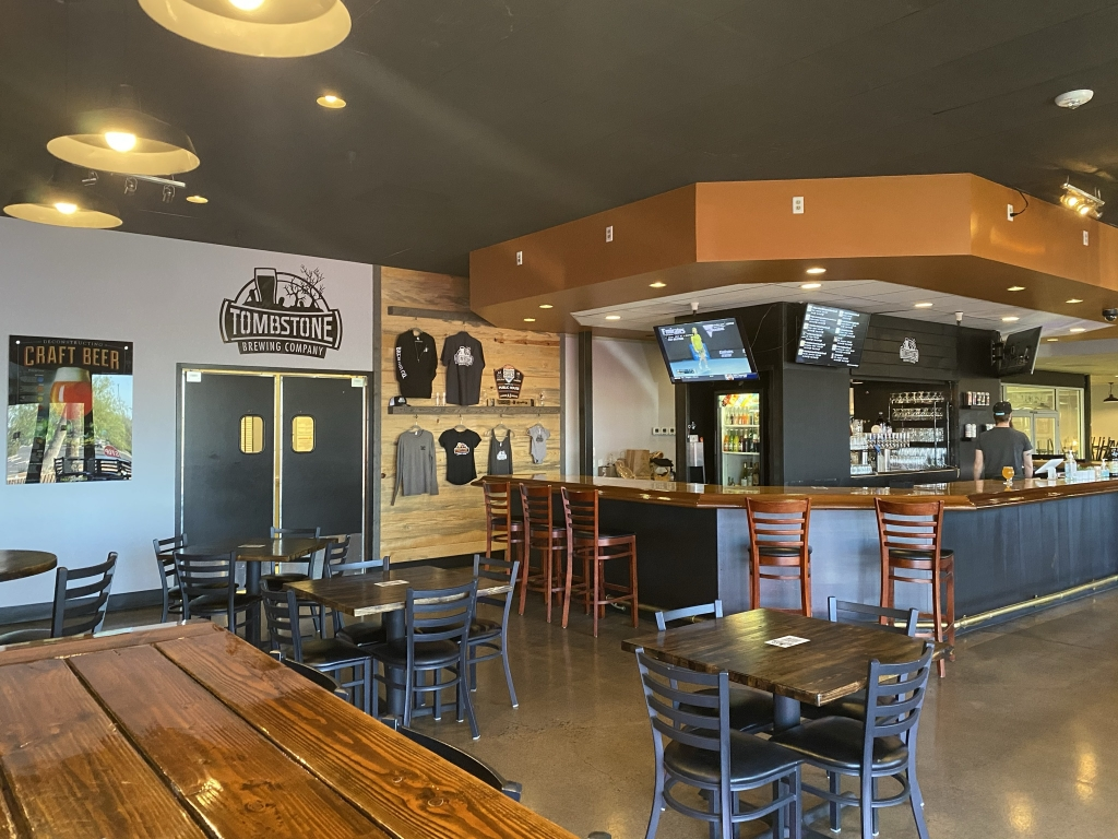 inside tombstone brewing phoenix showing the bar, apparel, and tables