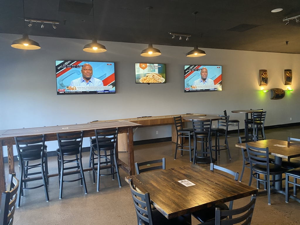 tombstone brewing interior with tvs on the wall, shuffle board, and tables